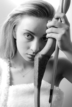 warrior girl: black and white picture of amazon warrior girl beautiful blond young woman holding bow and arrow close to herself, looking at camera on light wall background closeup portrait
