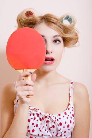 polka dot dress: Picture of pretty young woman in polka dot dress and curlers holding ping-pong racket. Charming girl on beige screen background. Stock Photo