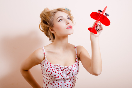 polka dot dress: Picture of beautiful young woman in polka dot dress and curlers holding toy plane. Charming girl on beige screen background. Stock Photo