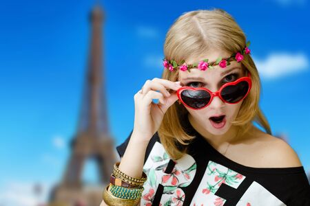 fancy girl: Portrait of beautiful excited woman in flower wreath and heart shaped glasses. Fancy girl shocked on Eiffel tower blurred background.