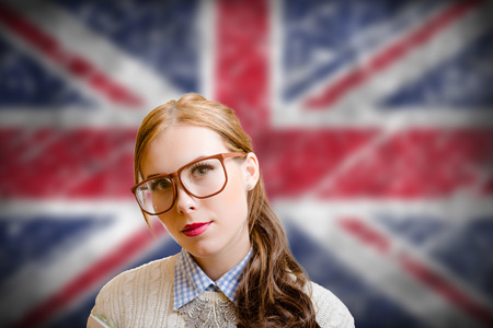 english girl: Portrait of beautiful young woman in big glasses and sweater. Student girl on english Union Jack blurred background.