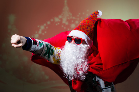forthcoming: Picture of funny Santa Claus wearing heart shape sunglasses and red coat flying like super man to be in time on bright festive bokeh background Stock Photo