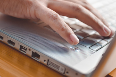 fingers on top: Picture of male hand typing on silver laptop. Closeup of fingers touching keyboard on blurred wood table top background.