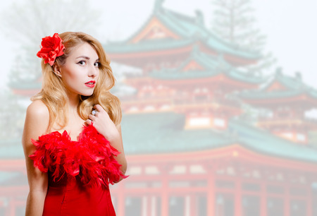 sexy blonde girl: Picture of beautiful young lady in red dress with flower barrette. Pretty girl on blurred japanese pagoda background.