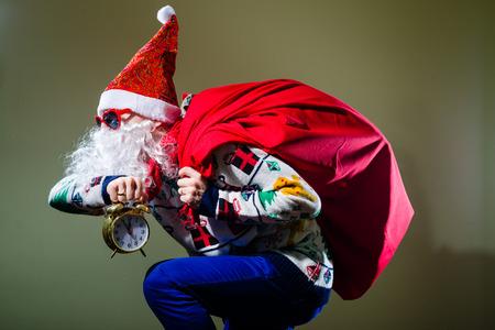 Bild der lustige Weihnachtsmann mit Wecker tragen Herz-Form-Sonnenbrille auf hellem festliche Bokeh Hintergrund