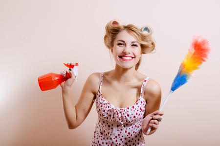 ama de casa: Retrato de mujer joven y bella en rulos con aerosol rojo y plumero de arco iris. Divertida niña muy sonriente feliz en el fondo de pantalla de color beige. Foto de archivo