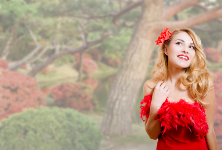 feather boa: Picture of beautiful young woman in red dress with feather boa. Pretty girl on blurred garden blossom background.