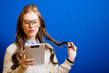 pcs: Teenager girl in glasses reading something on her tablet PC. Pretty girl touching her long brown curly hair and looking at tablet PCs screen. Stock Photo