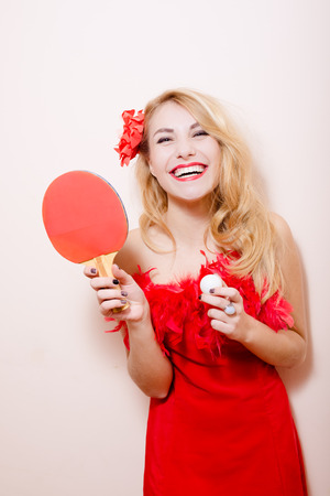 bat and ball: portrait of elegant attractive glamor pinup girl excited looking at camera posing in red dress with flower in hair, holding bat ball for table tennis on white or light copy space background closeup