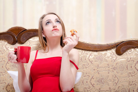 keep an eye on: sitting on bed or coach in red dress drinking tea and eating cake beautiful blonde young woman having fun looking up, copy space closeup portrait picture