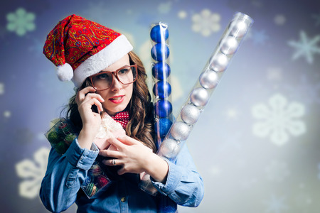 sexy elf: picture of making phone call, holding present box funny hipster girl in sunglasses wearing xmas santa hat over showflakes copy space background Stock Photo