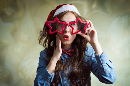 sexy xmas elf: Exciting looking at camera funny hipster beautiful young lady in super size star shape glasses wearing xmas santa hat over blured bokeh copy space background