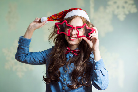superstar: Happy smiling and exciting looking at camera, funny hipster beautiful young lady in super size star shape glasses wearing xmas santa hat over showflakes copy space background