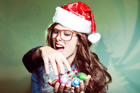 sexy christmas elf: biting intruders hand and saving Christmas tree decoration funny hipster girl in glasses wearing xmas santa hat over festive Christmas copy space background Stock Photo