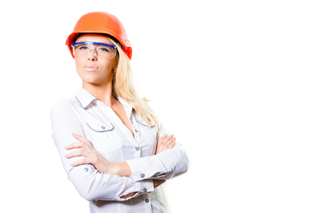 safety googles: Portrait of young attractive blond female  in white shirt wearing orange hard hat and safety glasses with her hands folded looking at camera, in studio over white background copyspace Stock Photo