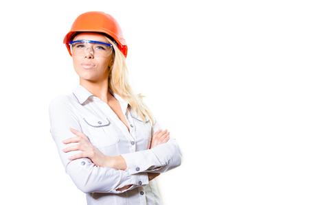 Portret van jong aantrekkelijk blond wijfje in wit overhemd die oranje bouwvakker en veiligheidsbril dragen met haar gevouwen handen het bekijken camera, in studio over witte achtergrond copyspace