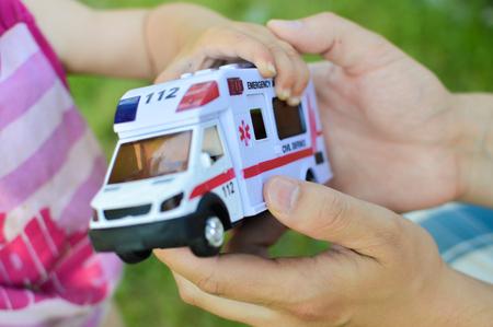 salvavidas: Una mano humana entregar un coche de juguete con la palabra de emergencia sobre ella a un niño demonstratiing concepto de salvamento