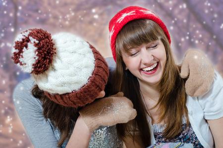 girls having fun: Portrait of two pretty brunette girls  having fun wearing winter hats and mittens in studio on bokeh background