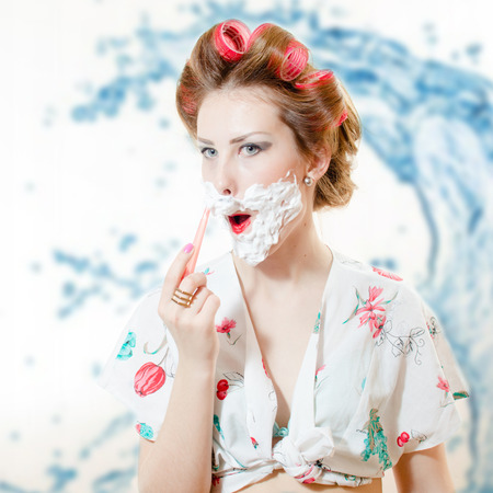 Beautiful young pinup woman shaving face with foam and razor looking in camera isolated on bokeh background closeup portrait