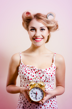 haircurlers: Picture of beautiful blonde smiling female with haircurlers holding retro clock in studio over pastel background