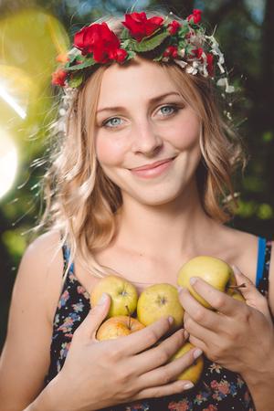 mujer con rosas: Hermosa joven rubia de vestido blanco y una corona de flores en verano al aire libre. Mujer al aire libre. Retrato del verano. chica rubia en las flores. Foto de archivo