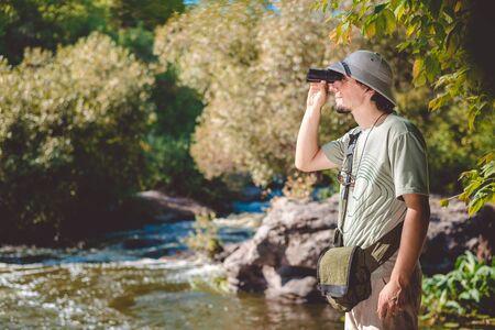 pith: El hombre que llevaba sombrero de explorador y camiseta de pie en la orilla rocosa usando los prism�ticos que miran lejos Foto de archivo
