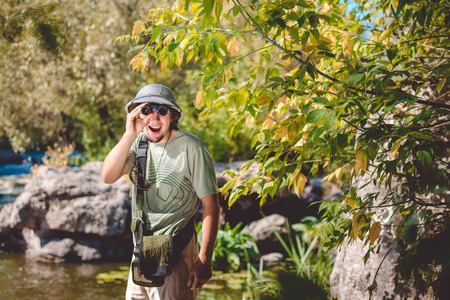 using binoculars: Man in pithhelmet standing on rocky riverbank using binoculars copyspace Stock Photo