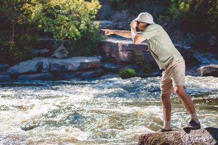 Man in pith helmet standing on rocky riverbank using binoculars leaning forward and pointing at something with his hand