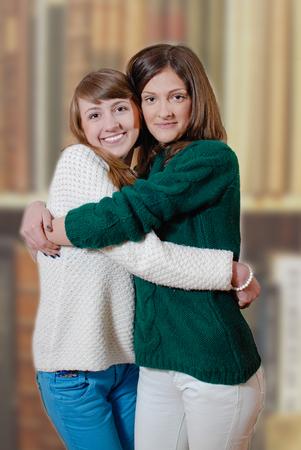 Dos adolescentes hermosos felices en casa hizo suéteres dando abrazan
