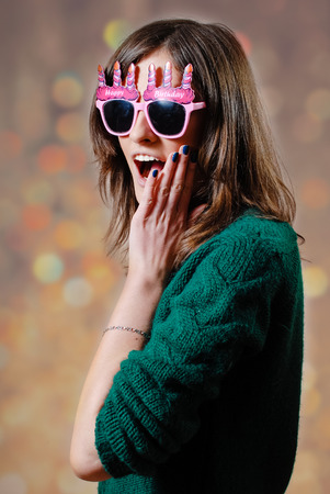 ridiculous: Young expressive female wearing sunglasses with pink funny spactackle frame making a silly expression on bokeh background copyspace