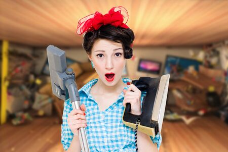 charlady: Young attractive pin up housewife in blue gingham shirt holding iron and hoover feeling overwhelmed copyspace Stock Photo