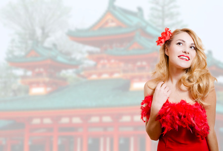 barrette: Picture of beautiful young lady in red dress with flower barrette. Pretty girl on blurred japanese pagoda background.