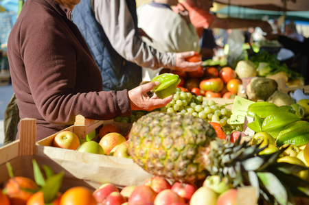 consumerism: Sale, consumerism concept and pineapple with fruits on grocery market stall background. Closeup on person hand shopping for fresh food