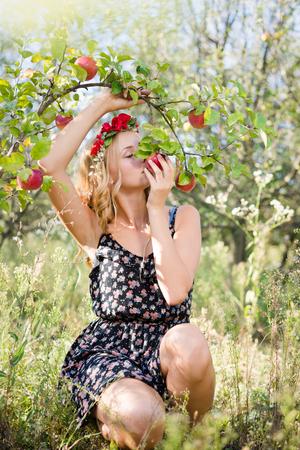 ziemlich Apfel Fee: junge Frau cute blonde Mädchen unter roten Äpfel mit Blumenkranz und Sonne Licht von Fackeln Strahlen Lächeln in die Kamera schaut auf Sommer im Freien Kopie Raum Hintergrund