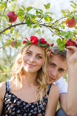 personas abrazadas: Closeup portrait of happy young couple in bohemian style hugging in autumn orchard among ripe apples on green outdoors background