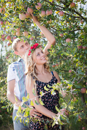 Portrait of happy young couple in bohemian style hugging in autumn orchard among ripe apples on green outdoors background