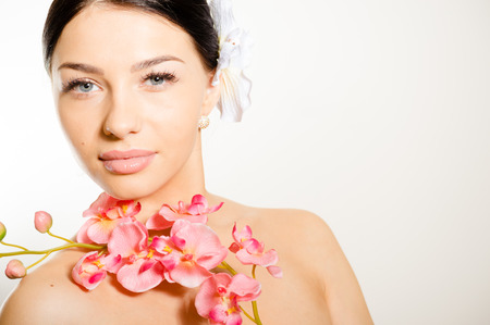 adult care: Adult woman with beautiful face and white flowers. Skin care concept. Stock Photo