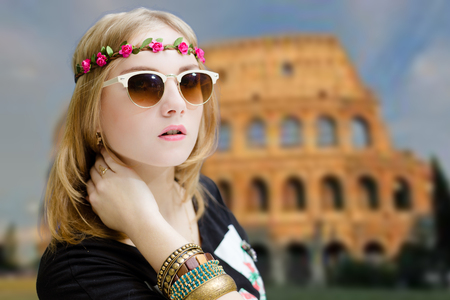 fancy girl: Portrait of beautiful young woman in charming flower wreath and ethnic bracelets. Fancy girl in sunglasses on Colosseum blurred background.