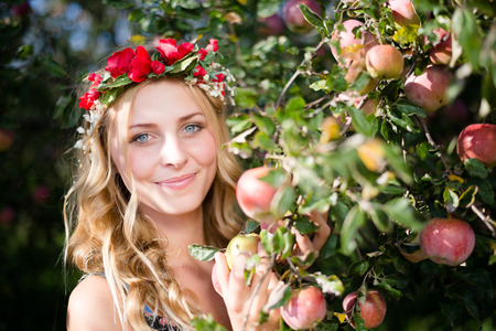 Closeup portrait of young beautiful lady smiling among red apples with wreath of flowers. Blond sexy girl on summer outdoor copy space background