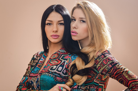 splice: Image of beautiful blonde and brunette sisters standing together with their hair plait together