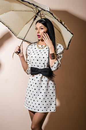 polka dot dress: Young happy pinup woman with umbrella wearing polka dot dress over white background