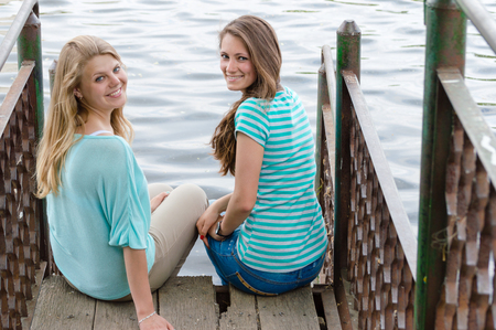 bridge over water: Friendship. Best friends sitting on bridge over water copy space background Stock Photo