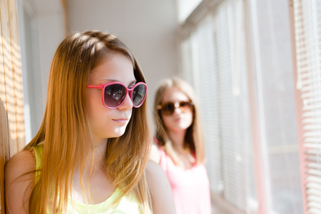 betray: closeup portrait of 2 beautiful blond young women standing in distance from each other upset on sunny windows background Stock Photo