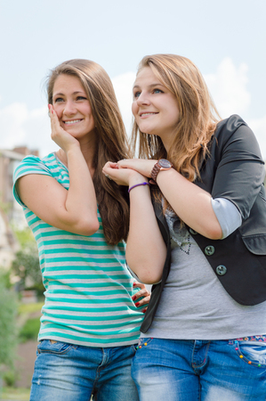 background skype: Friendship concept. Two smiling girls over blue skype outdoors background
