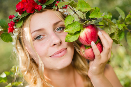 Closeup portrait of young beautiful lady smiling among red apples with wreath of flowers. Blond sexy girl looking at camera on summer outdoor copy space background