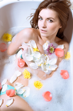 body milk: Spa body care for sensual relaxation: picture of beautiful sexy young woman pinup girl having fun relaxing in bath with flowers petals on milk copy space water background.