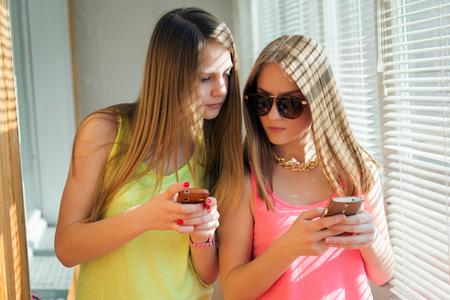 Dos adolescentes mirando en sus aparatos, mientras que por otra en la ventana soleada Foto de archivo