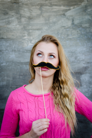 fake smile: Portrait of surprised pretty girl holding funny mustache on stick. Joyful young woman ready for party, on copy space background