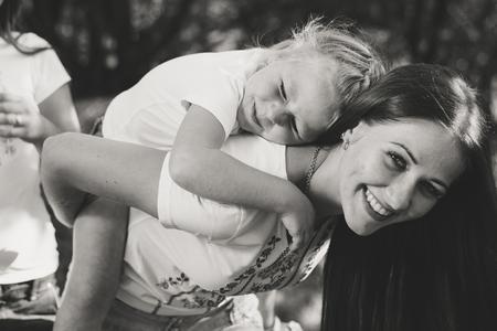 Joven y bella mujer lleva en su espalda y niña feliz sonriendo al aire libre foto en blanco y negro