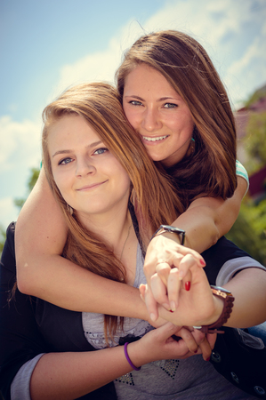 background skype: Friendship concept. Two happy smiling girls hug over blue skype outdoors background